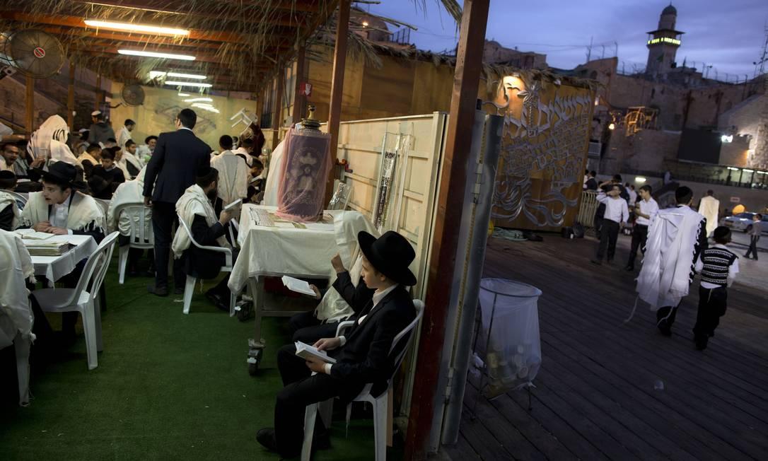 As orações seguem sob a cabana montada na forma descrita nas escrituras sagradas Oded Balilty / AP