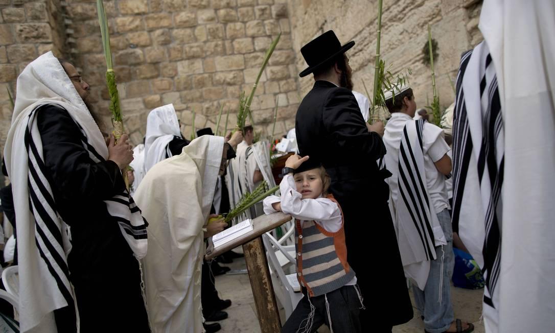 Coberto com seus xales os religiosos oram segurando o molho de Sucôt, com as quatro espécies Oded Balilty / AP
