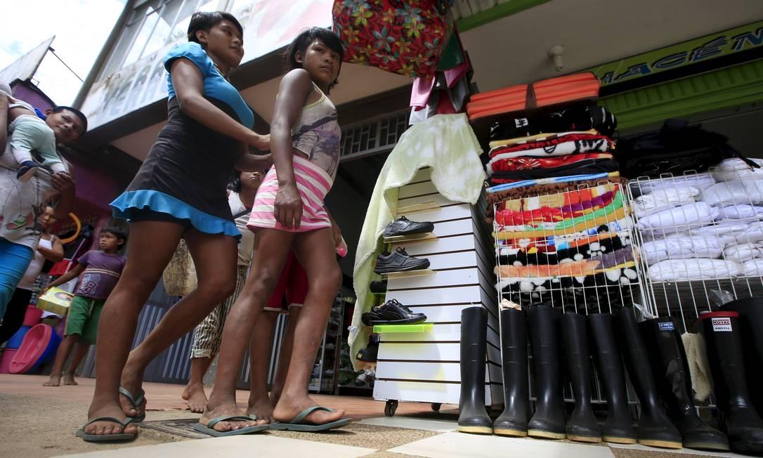 Meninas da tribo Nukak Maku, de índios colombianos, passeiam nas ruas da província de Guaviare a 400 km de Bogotá. Sairam da floresta em 2005, em seu estado natural, semi-nus, e fumando seus cachimbos. Hoje vivem em campos de refugiados, distante de suas tradições JOHN VIZCAINO / REUTERS