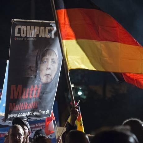 Manifestantes protestam contra política de recepção a refugiados proposta pela chanceler Angela Merkel Foto: Jens Meyer / AP