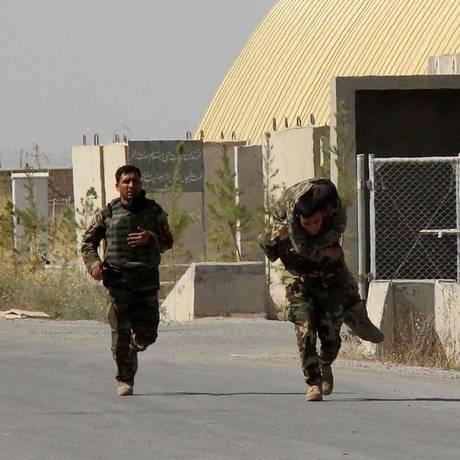 Soldados do Exército resgatam colega ferido em operação Foto: STR / AFP
