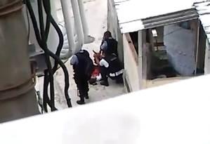 Agachado, um PM segura a mão direita de Eduardo, na qual colocou uma arma para forjar um confronto Foto: Reprodução