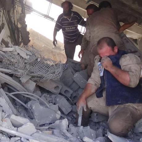 Imagem divulgada pela Defesa Civil síria mostra equipes de resgate procurando sobreviventes entre destroços de casa na cidade de Talbiseh após um bombardeio Foto: AP