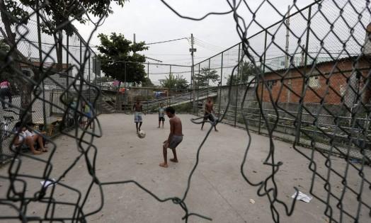 Meninos brincam em quadra da Favela do Jacarezinho e reclamam das condições do alambrado Foto: Domingos Peixoto / Agência O Globo