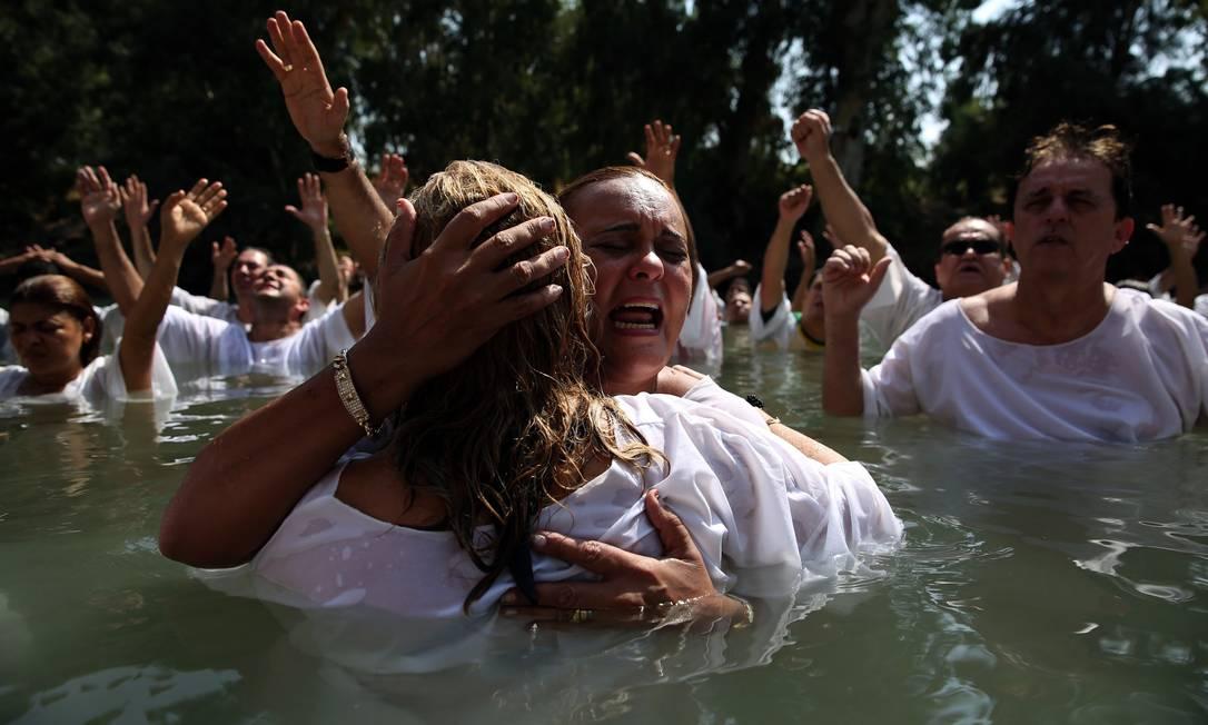 Cristãos evangélicos brasileiros rezam durante um ritual de batismo coletivo nas águas do Rio Jordão, no nordeste de Israel, fronteira com a Jordania GALI TIBBON / AFP