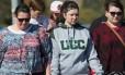 Estudantes e funcionários da Umpqua Community College chegam ao campus, um dia após tragédia