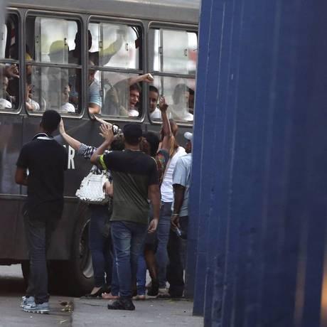 Um grupo fala com detentos que foram colocados em um ônibus Foto: Domingos Peixoto / Agência O Globo