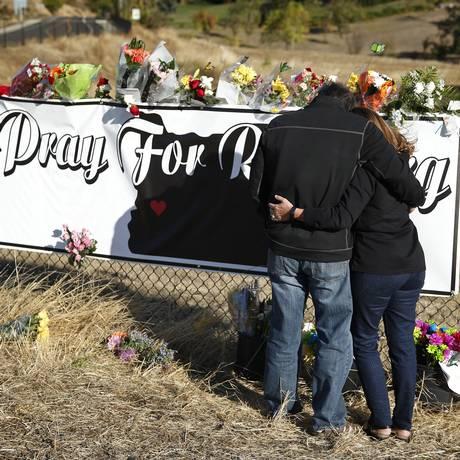 Colegas de alunos mortos deixam flores em memorial para as vítimas do ataque no Oregon Foto: John Locher / AP