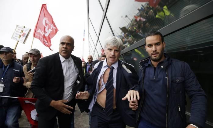 Com a camisa rasgada, diretor da Air France em Orly, Pierre Plissonnier, é ajudado por seguranças após ataque de manifestantes, que invadiram o escritório da empresa durante reunião do comitê central KENZO TRIBOUILLARD / AFP