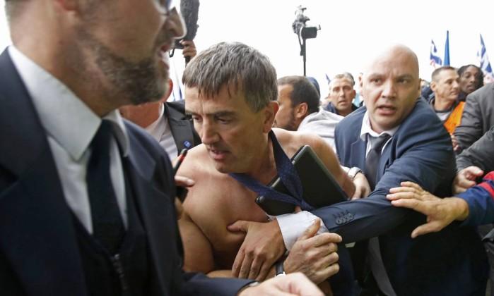 Sem camisa, Xavier Broseta, diretor de RH da Air France, é escoltado por seguranças após a invasão da sede da empresa JACKY NAEGELEN / REUTERS