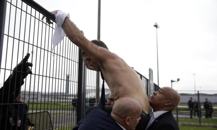 Com o que restou de sua camisa amarrada na mão, Xavier Broseta, diretor de Recursos Humanos da Air France, escala uma grade na fuga de manifestantes contrários à demissão de quase 3 mil profissionais KENZO TRIBOUILLARD / AFP
