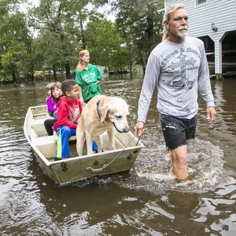 Família sai com barco após inundação em Conway Foto: Jason Lee / AP