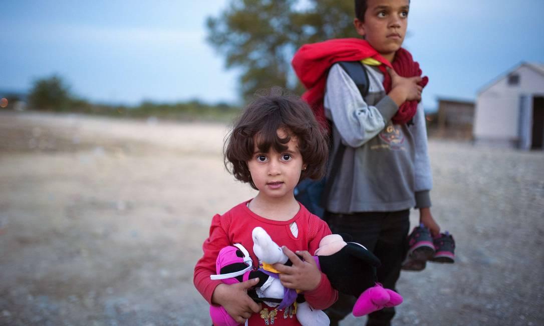 Uma menina é fotografada com grupo de imigrantes em um campo de registro depois de atravessar a fronteira entre a Grécia e a Macedônia Foto: ROBERT ATANASOVSKI / AFP