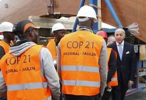 Operários cruzam com o Ministro das Relações Exteriores da França, Laurent Fabius, durante sua visita ao local onde será realizada a 21ª Conferência do Clima, em Le Bourget Foto: JACKY NAEGELEN / REUTERS