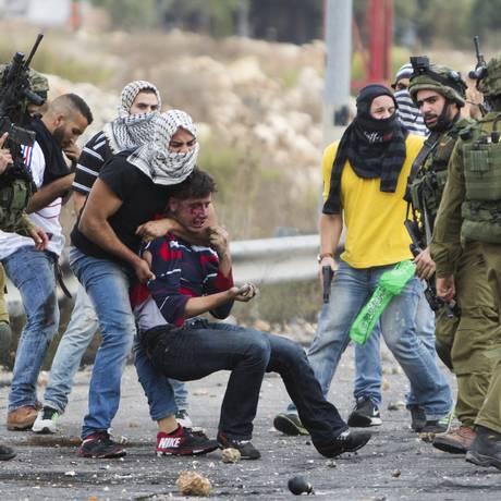 Policiais israelenses à paisana e soldados israelenses prendem um manifestante palestino ferido perto de Ramallah, na Cisjordânia Foto: Majdi Mohammed / AP