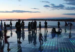 """Os painéis de """"Saudação ao sol"""", no chão na orla de Zadar, brilham ao anoitecer Foto: Eduardo Maia"""