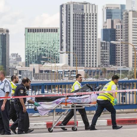 Médicos transportam corpo de palestino morto com um tiro após esfaquear soldado israelense e três vítimas em Tel Aviv Foto: Jack Guez / AFP