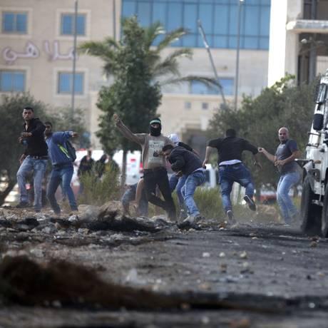 Manifestantes jogam pedras contra policiais perto de Ramallah: situação se deteriora Foto: Majdi Mohammed / AP