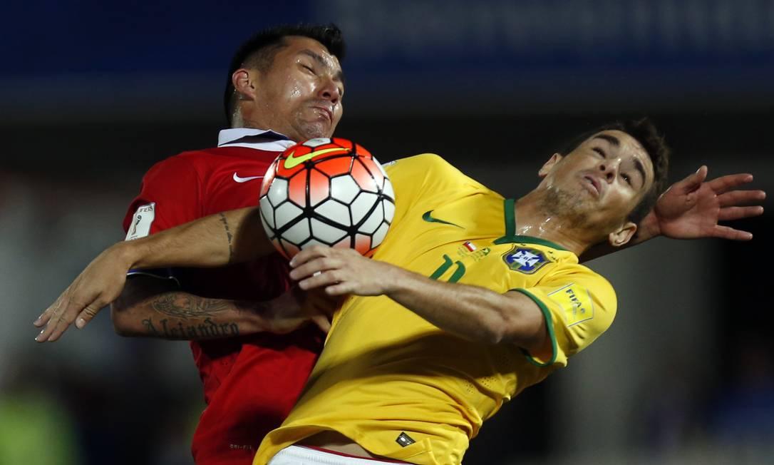O chileno Medel e o brasileiro Oscar no duelo em Santiago Luis Hidalgo / AP