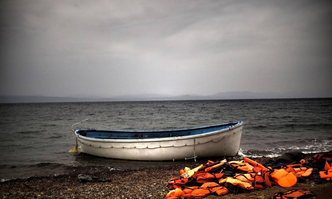 Coletes salva-vidas e um bote usado por refugiados na ilha de Lesbos: máfias lucram com a travessia Foto: ARIS MESSINIS / AFP