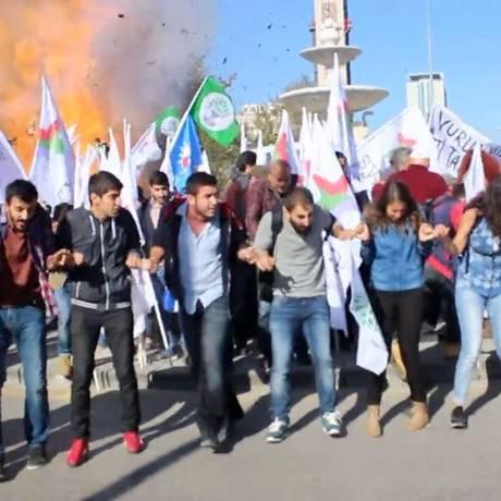 Imagem retirada de vídeo mostra grupo de jovens cantando de mãos no momento da primeira explosão em Ancara Foto: HO / AFP