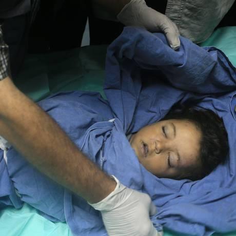 Um médico cobre o corpo da menina palestina Rahaf Hasan, de 2 anos, morta junto com a mãe, que estava grávida, durante um ataque aéreo israelense Foto: MOHAMMED ABED / AFP