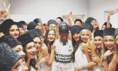 Hamilton em foto postada por ele no Twitter com modelos russas: feliz da vida após vitória que o aproxima mais do tricampeonato Foto: Reprodução