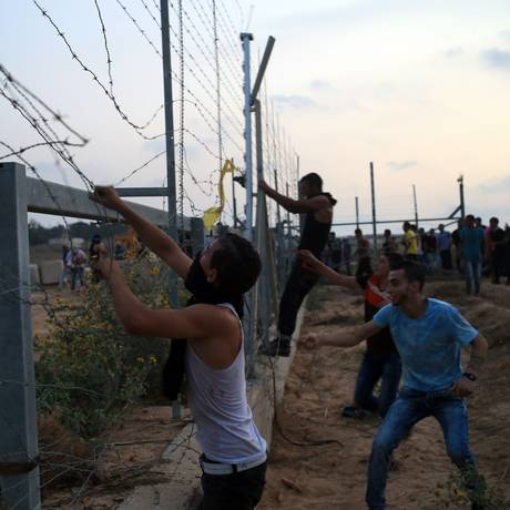 Manifestantes palestinos derrubam parte de uma cerca na fronteira entre Israel e a Faixa de Gaza durante confrontos com as forças de segurança israelenses Foto: MOHAMMED ABED / AFP