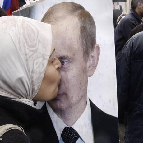 Uma mulher beija uma foto do presidente russo, Vladimir Putin, durante um protesto pró-governo sírio em frente à embaixada russa em Damasco Foto: Muzaffar Salman / AP