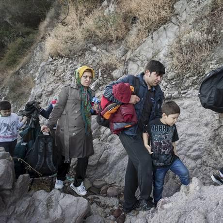 Após cruzarem o Mar Egeu, afegão atravessam pedras em Lesbos Foto: FOTIS PLEGAS G / REUTERS