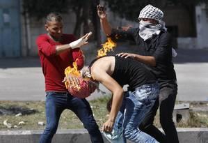 Palestinos apagam fogo em colega após ele se queimar com a própria garrafa de coquetel molotov, em Hebron Foto: MUSSA ISSA QAWASMA / REUTERS