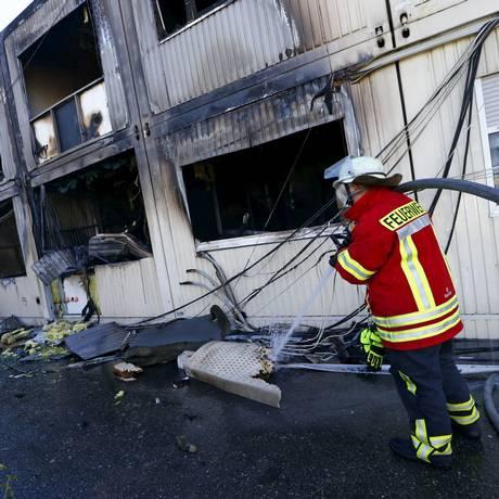 Bombeiro alemão inspeciona abrigo de refugiado queimado em Rottenburg, Alemanha. Políticos criticam onda de incêndios pelo país Foto: Ralph Orlowski / Reuters