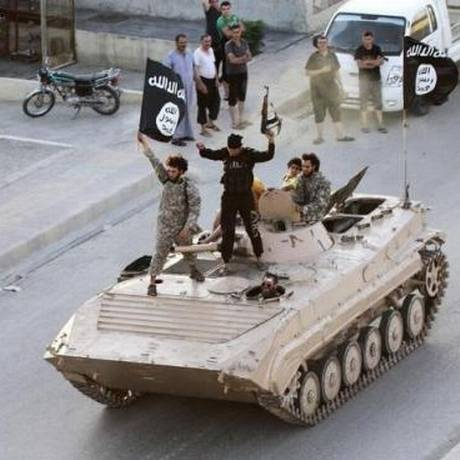 Militantes do Estado Islâmico carregam bandeira da organização durante desfile militar nas ruas de Raqqa em junho de 2014 Foto: Reuters