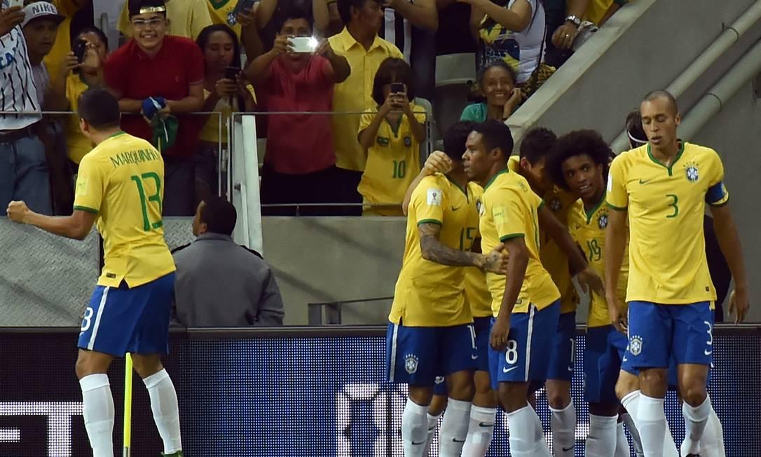 Willian, à direita, é abraçado ao fazer 1 a 0 para o Brasil NELSON ALMEIDA / AFP