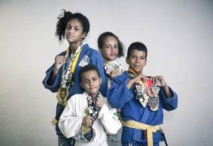 Mayara, Kelly, Felipe e João Pedro posam com as medalhes conquistadas em campeonatos de Jiu-Jítsu e Judô Foto: Leo Martins/ Agência O Globo