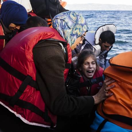 Menina chora enquanto chega com outros imigrantes e refugiados à ilha grega de Lesbos Foto: DIMITAR DILKOFF / AFP
