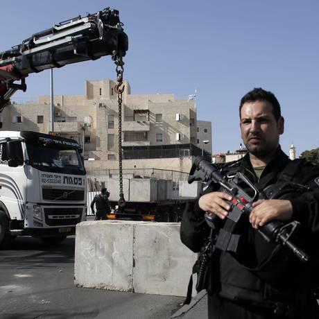 Cidade partida. Militares acompanham instalação de bloqueio na divisa entre bairros palestinos e judaicos de Jerusalém. Medida foi motivada por onda de violência Foto: AHMAD GHARABLI/AFP