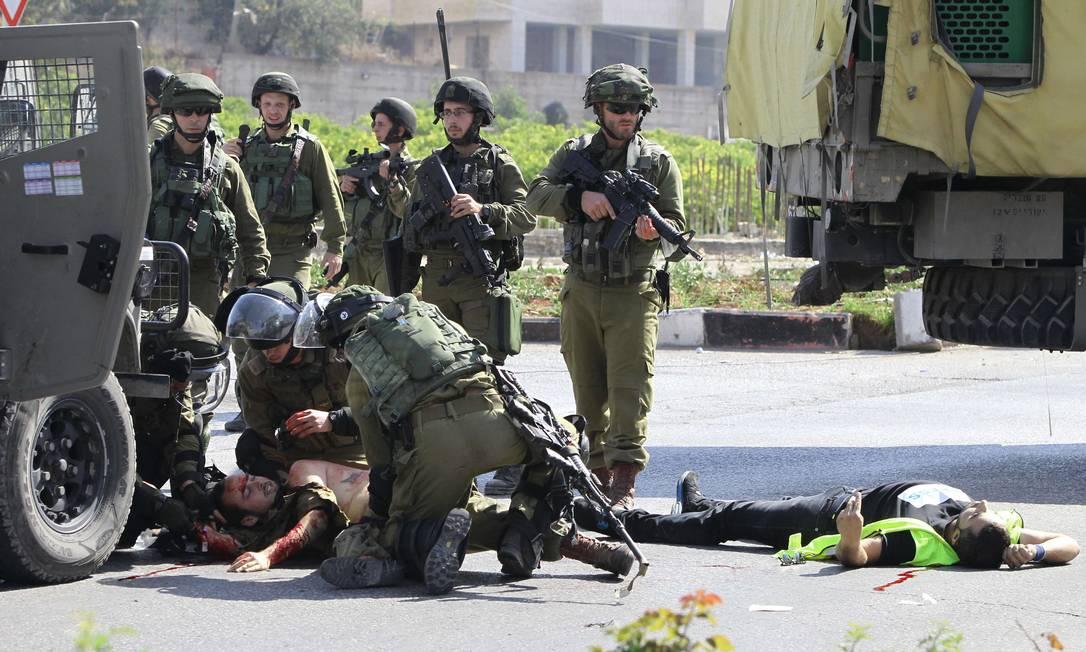 Grupo de militares israelenses se une para tratar soldado ferido ao lado do palestino baleado Foto: HAZEM BADER / AFP