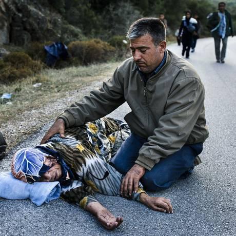 Curdo sírio auxilia sua mãe, que desmaiou após travessia do Egeu para Lesbos Foto: DIMITAR DILKOFF / AFP