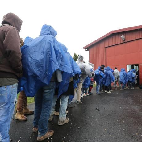 Migrantes fazem fila para se registrarem na cidade de Lendava, na fronteira entre Croácia e Eslovênia Foto: Borut Zivulovic / AFP