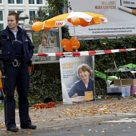 Uma policial monta guarda perto de um posto de campanha da candidata independente Henriette Reker, na cidade de Colônia. Eleita, ela foi esfaqueada por um radical de direita por apoiar a entrada de refugiados Foto: WOLFGANG RATTAY / REUTERS