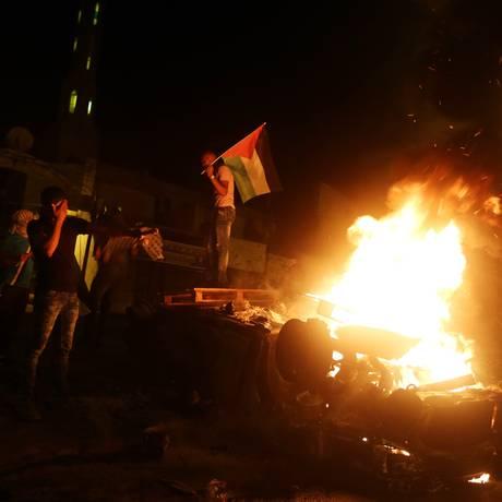 Jovens palestinos balançam a bandeira nacional enquanto o túmulo de José pega fogo Foto: JAAFAR ASHTIYEH / AFP