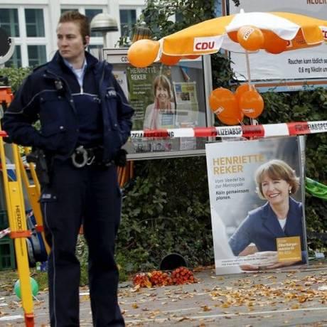Uma policial monta guarda perto de um posto de campanha da candidata independente Henriette Reker, na cidade de Colônia Foto: WOLFGANG RATTAY / REUTERS