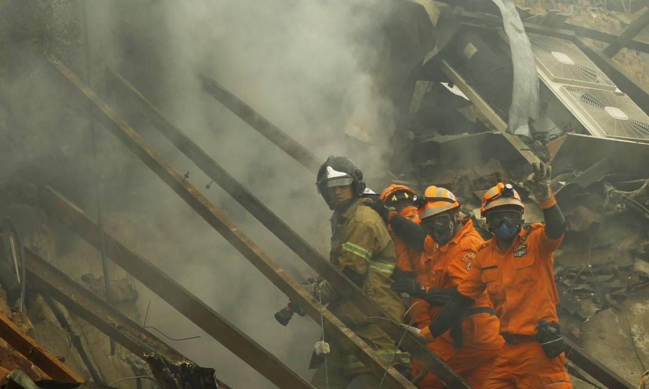 Bombeiros trabalham nos escombros ainda com muita fumaça Foto: Gabriel de Paiva / Agência O Globo