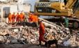 Bombeiros trabalham na busca de vítimas e de pertences dos moradores
