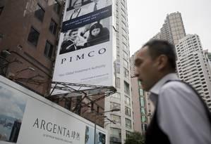 Pedestre passa em frente a propaganda da Pimco em Hong Kong Foto: Brent Lewin / Bloomberg News