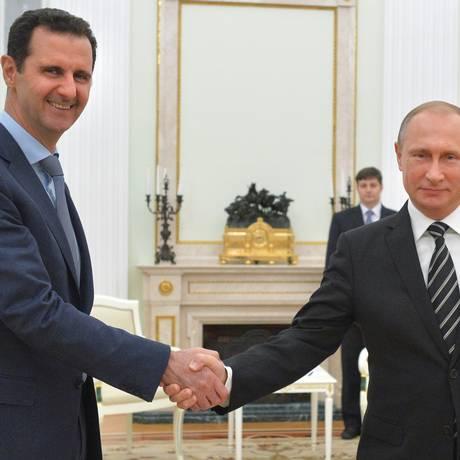 Vladimir Putin e Bashar al-Assad apertam as mãos durante encontro em Moscou Foto: Alexei Druzhinin / AP
