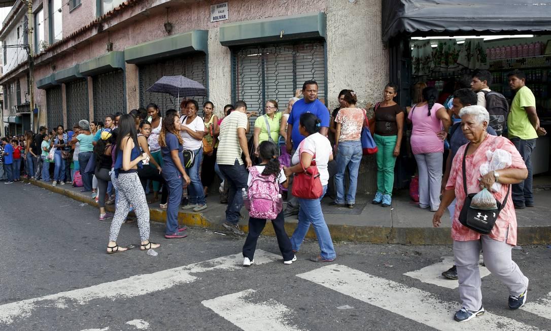 Venezuelanos fazem fila do lado de fora de um supermecado em Caracas Foto: / CARLOS GARCIA RAWLINS/REUTERS