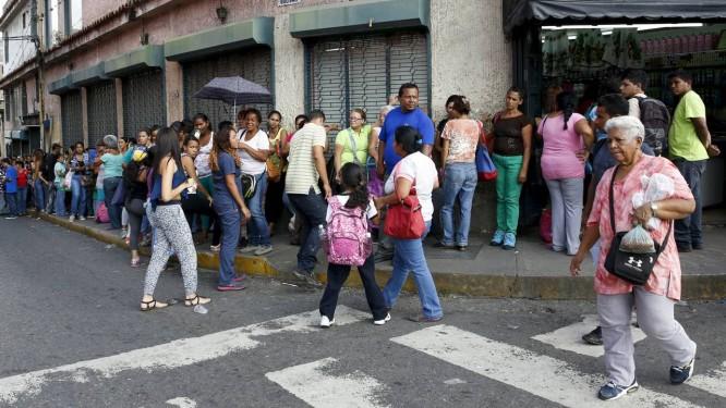 Venezuelanos fazem fila do lado de fora de um supermecado em Caracas Foto: CARLOS GARCIA RAWLINS/REUTERS