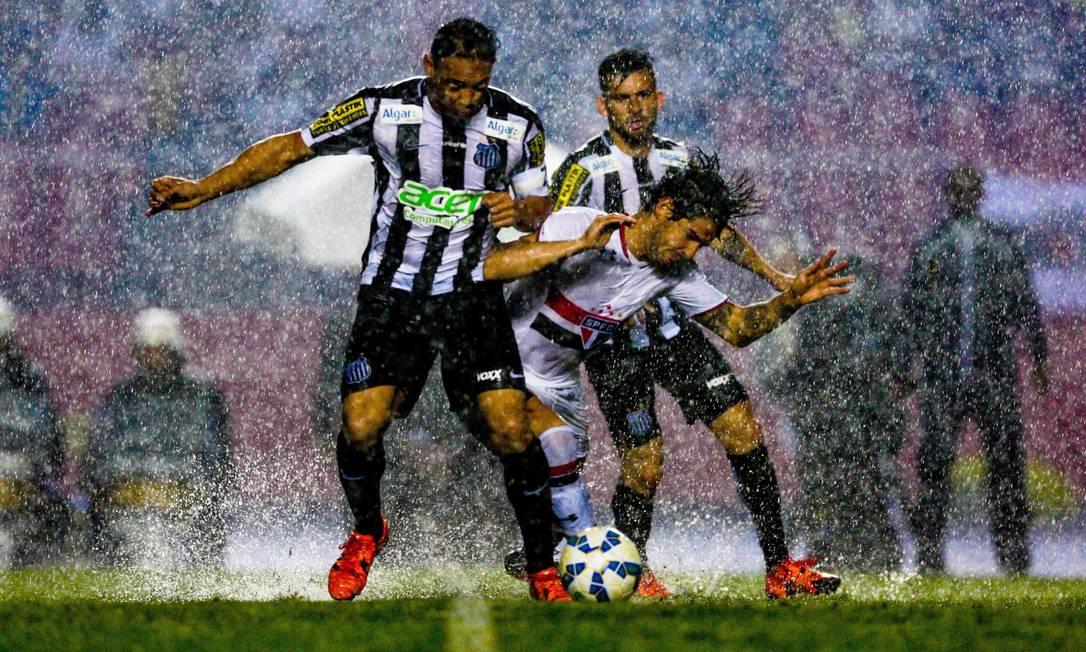 São Paulo x Santos no Morumbi: debaixo de muita chuva, Pato tenta se livrar da marcação Pedro Kirilos / Agência O Globo